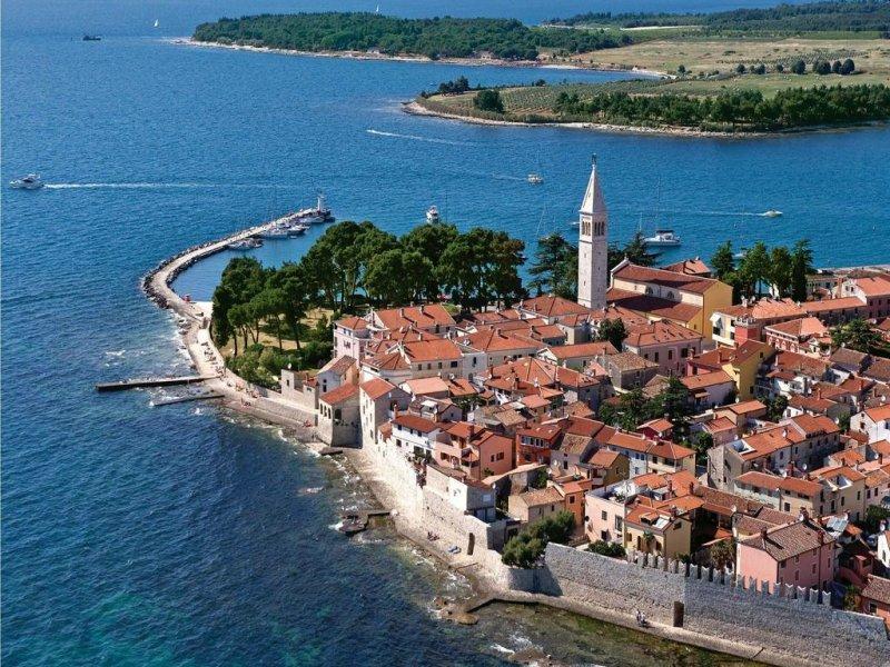 Novigrad con la sua città vecchia aggrappata alla riva e un campanile che si erge sopra un'infarinatura di tetti di tegole arancioni.