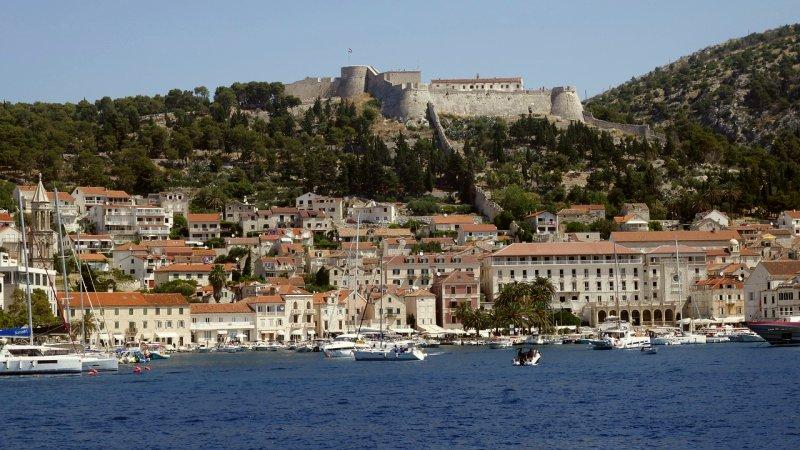 La città di Hvar si estende attorno al porto sottostante, mentre le isole al largo di Hvar e l'isola di Vis sono visibili più lontano.